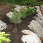 Boulders placed to retain flower beds in retaining wall